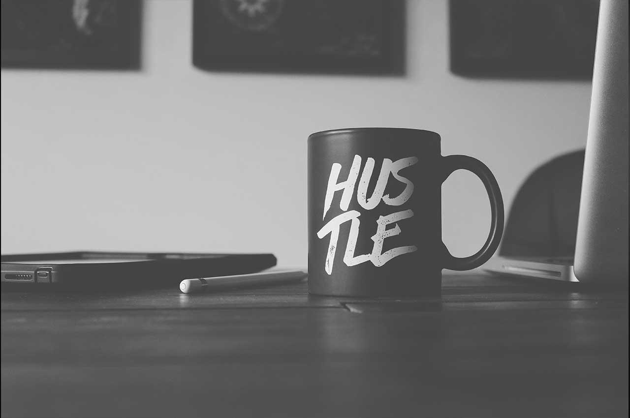 Kaffebecher mit Aufschrift hustle in schwarz-weiß