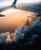 Heckflügel eines Flugzeugs über den Wolken für Restplatzbörse als Kunde von Slidebird